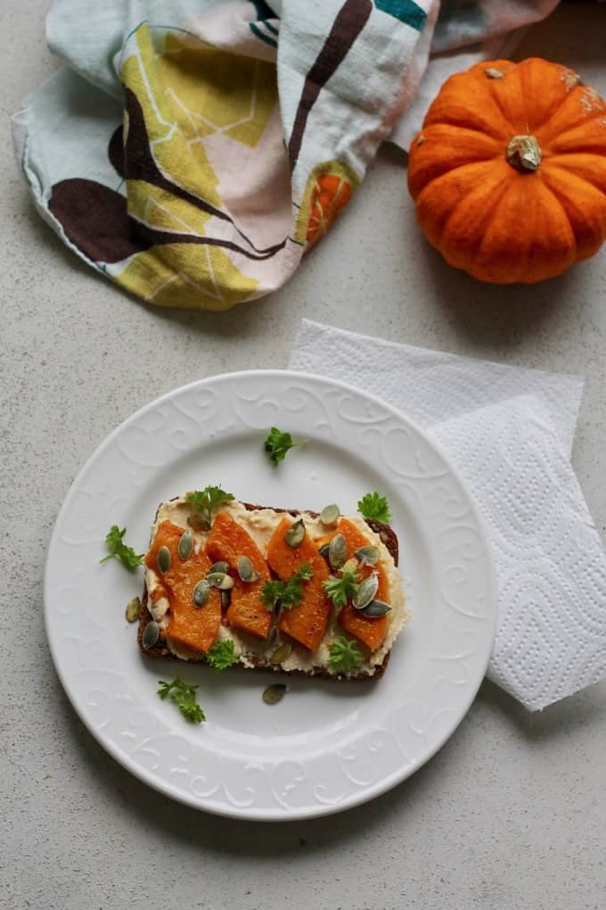 Roasted butternut squash and hummus on rye toast sprinkled with parsley and pumpkin seeds