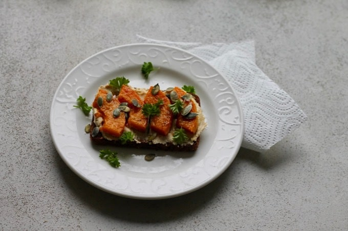 Roasted butternut squash and hummus on rye toast on a white plate