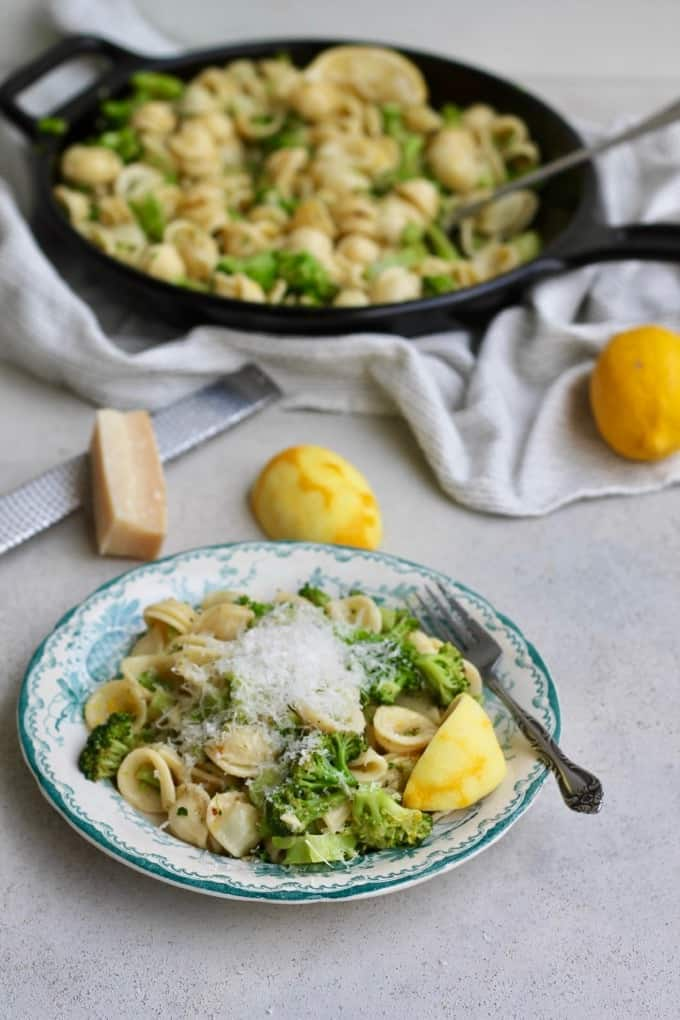 orecchiette with broccoli and lemon portrait with a plate of pasta in front of a skillet