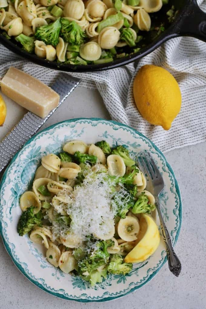 orecchiette with broccoli and lemon on a green patterned plate with lemon and parmesan
