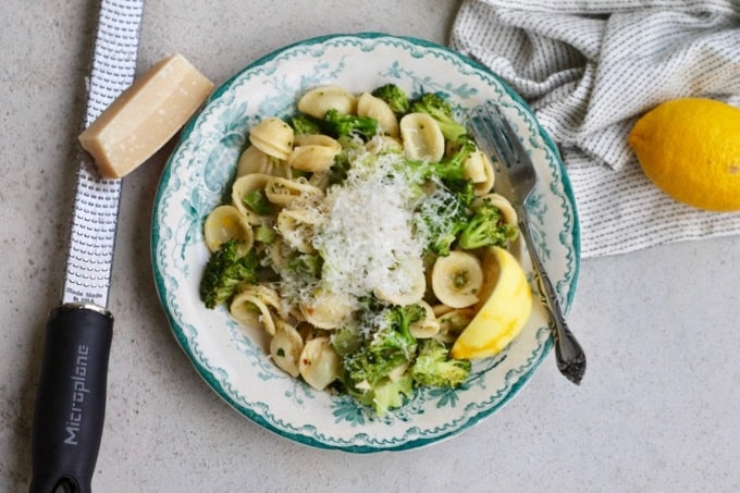 orecchiette with broccoli and lemon on a patterned plate with lemons and parmesan