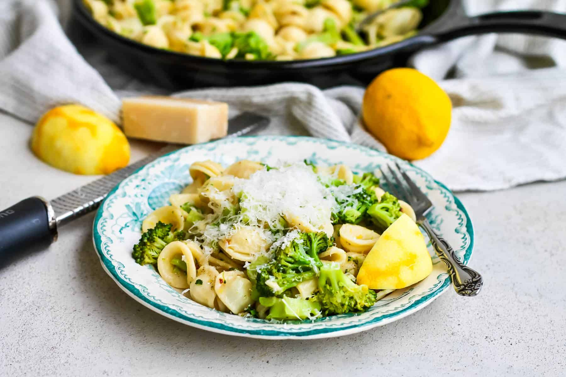 a blue patterned plate with broccoli orecchiette