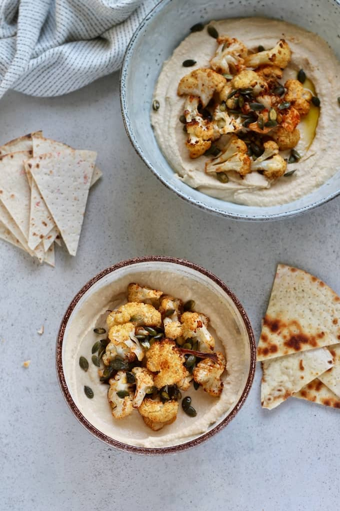 portrait photo with two bowls of hummus and roasted cauliflower on a grey background