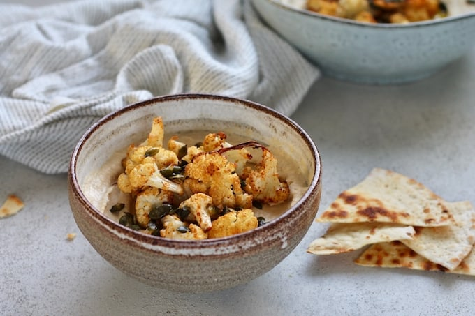 two bowls of hummus topped with roasted cauliflower