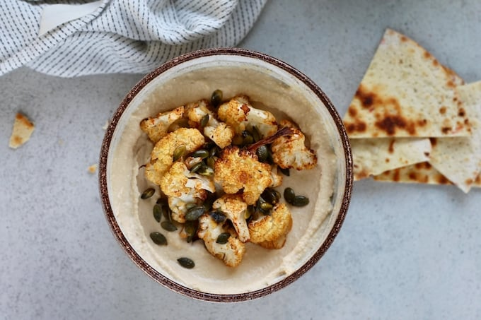 a brown bowl of hummus topped with roasted cauliflower