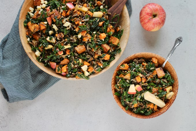 two wooden bowls with wild rice salad on a grey background with an apple