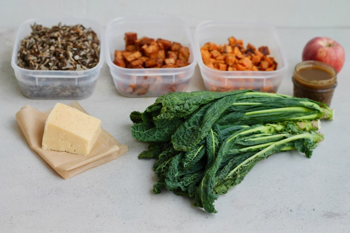 wild rice, roasted sweet potato, spicy tofu, cheese, and kale on a grey background