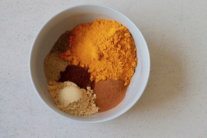 turmeric, ginger, cinnamon, cardamom, cloves, and black pepper in a blue bowl