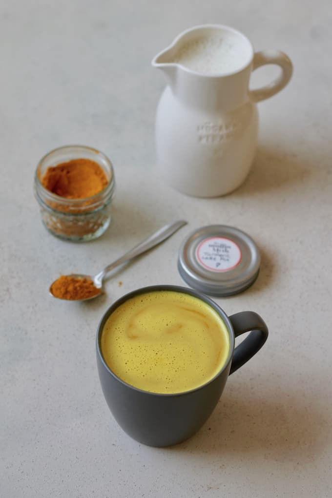turmeric latte in a black mug on a grey background, with turmeric latte mix and milk in the background
