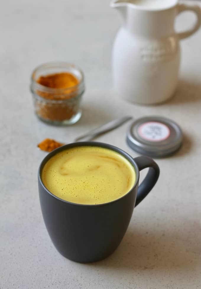 turmeric latte in a black mug with oat milk and turmeric latte mix in the background