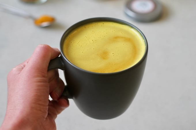 a hand holding a turmeric latte in a black mug