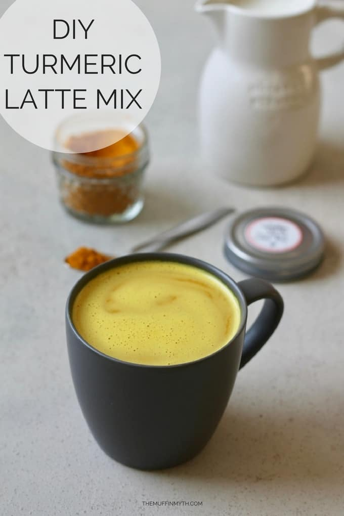 turmeric latte in a black mug with oat milk and turmeric latte mix in the background with text overlay reading turmeric latte mix