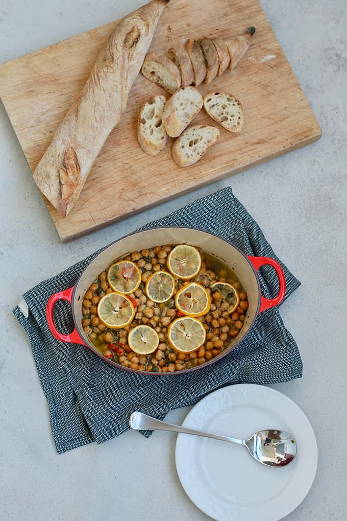 overhead shot of braised chickpeas in a red dutch oven with a baguette on a cutting board and a white plate