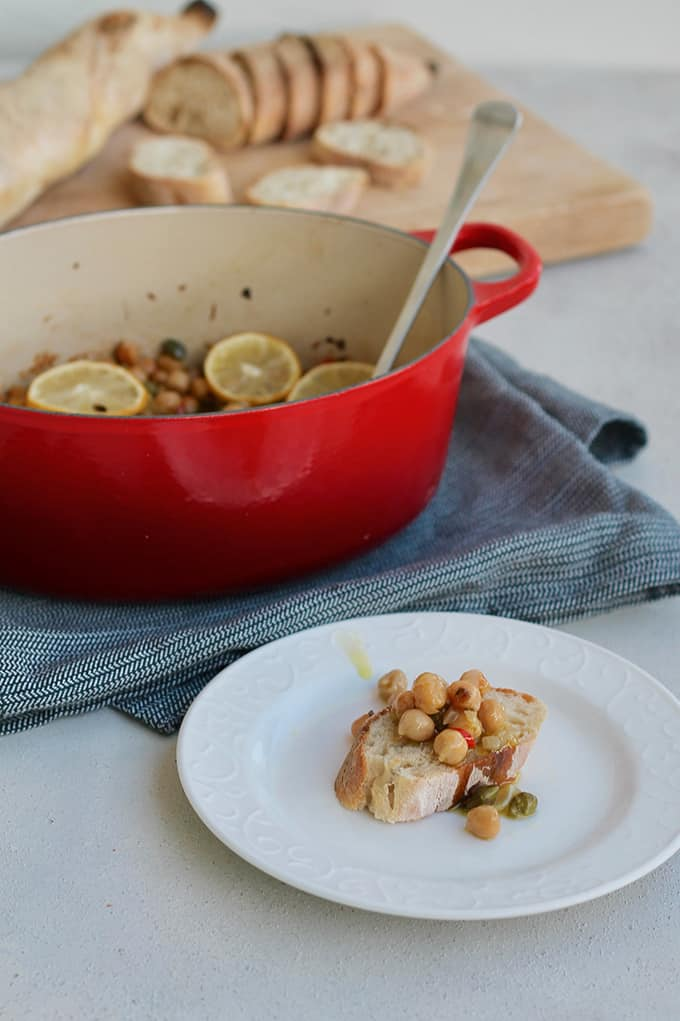 olive oil braised chickpeas on a piece of bread on a white plate