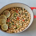 braised chickpeas in a red dutch oven with lemon slices on top