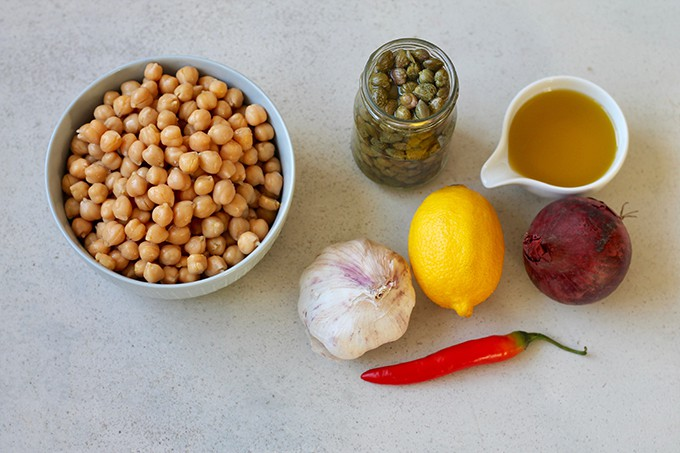 chickpeas, capers, olive oil, lemon, onion, and pepper on a grey background
