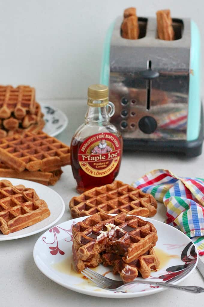 sweet potato gingerbread waffles on a white plate with maple syrup and a toaster in the background