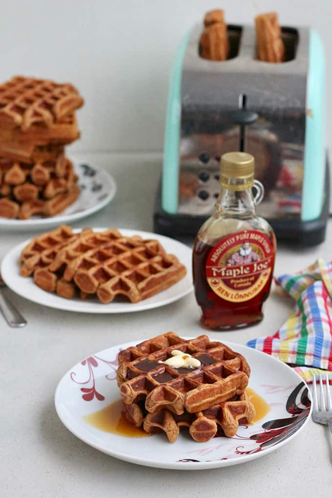 sweet potato waffles on a white plate with a toaster in the background
