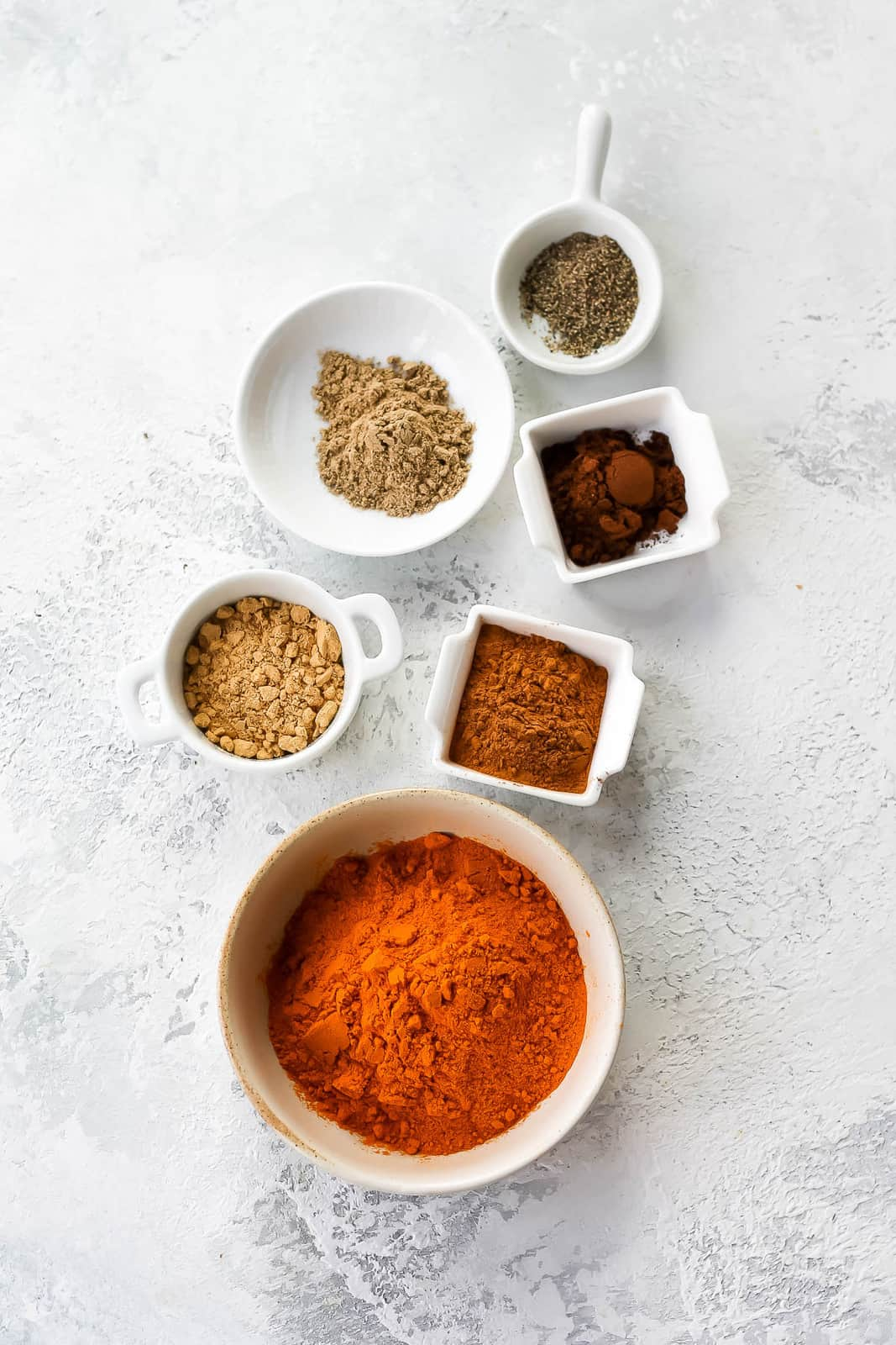 turmeric, cinnamon, ginger, cardamom, cloves and black pepper on a grey background