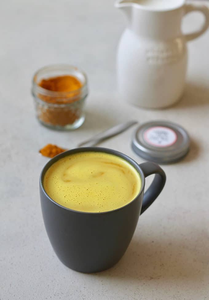 A turmeric latte in a dark grey mug with a jar of turmeric latte mix in the background