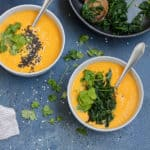 overhead shot of carrot soup topped with cooked greens and sprinkled with sesame seeds