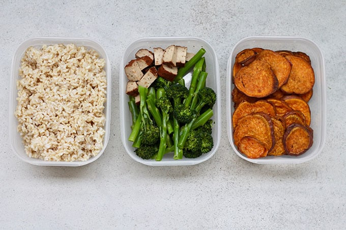 cooked brown rice, steamed broccoli, diced tofu, and roasted sweet potatoes in tupperware containers