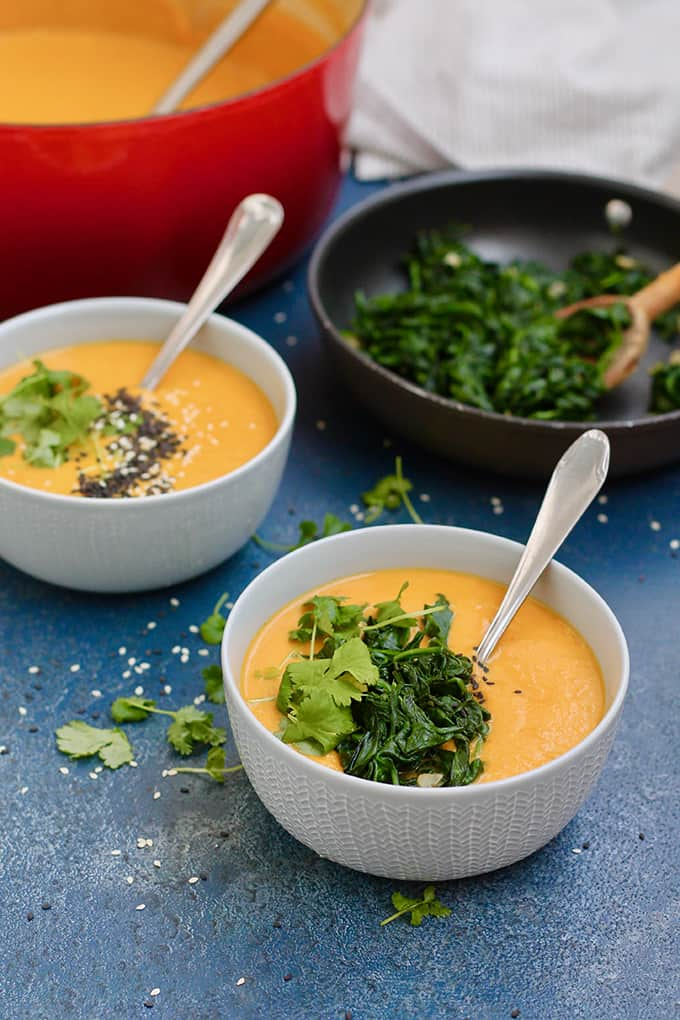 carrot and tahini soup topped with greens in blue bowls