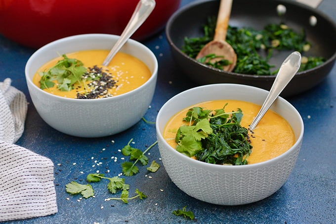 landscape shot of carrot tahini soup in blue bowls