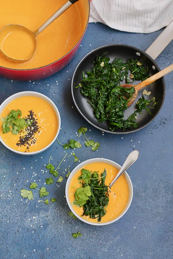 overhead shot of carrot tahini soup in blue bowls and a small frying pan of cooked garlicky greens