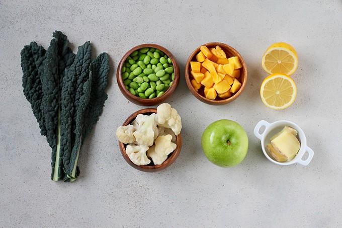 kale, edamame, cauliflower, mango, green apple, lemon, and ginger arranged in rows on a grey background