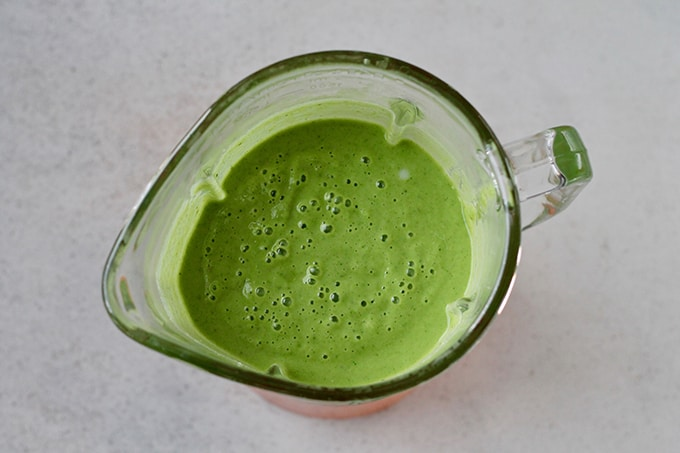 overhead shot of green smoothie in a blender
