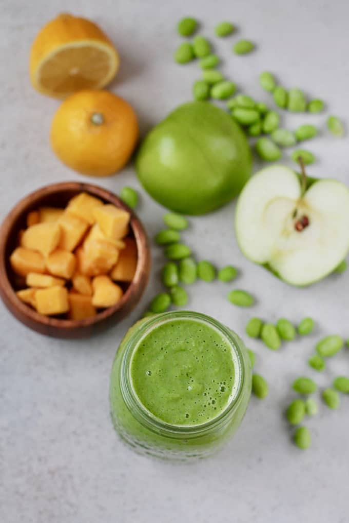 green smoothie with mango, kale, edamame, lemon, and green apple on a grey background