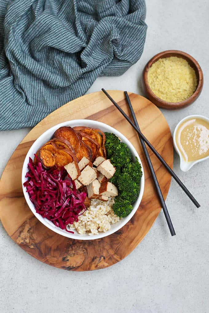overhead portrait shot of brown rice and winter vegetables in a white bowl with chopsticks and sauce in the background