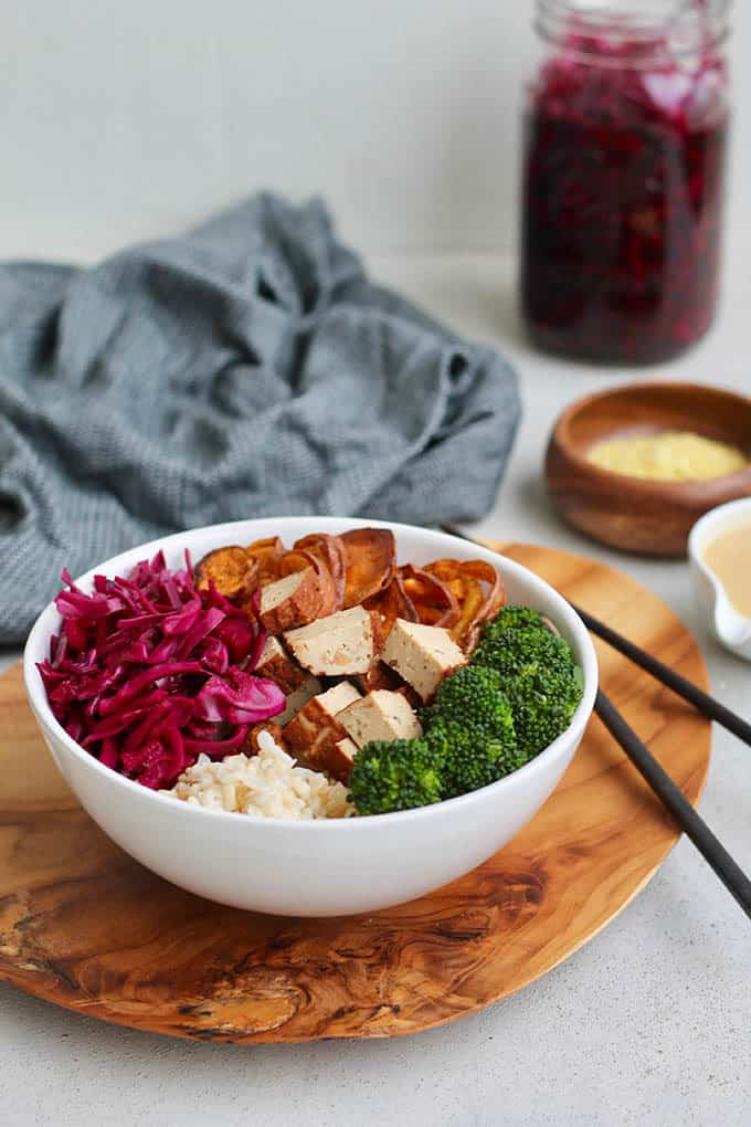 white bowl with broccoli, brown rice, tofu, red cabbage, and sweet potato