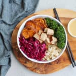 broccoli, sweet potatoes, red cabbage, tofu, and brown rice in a white bowl on a wooden platter