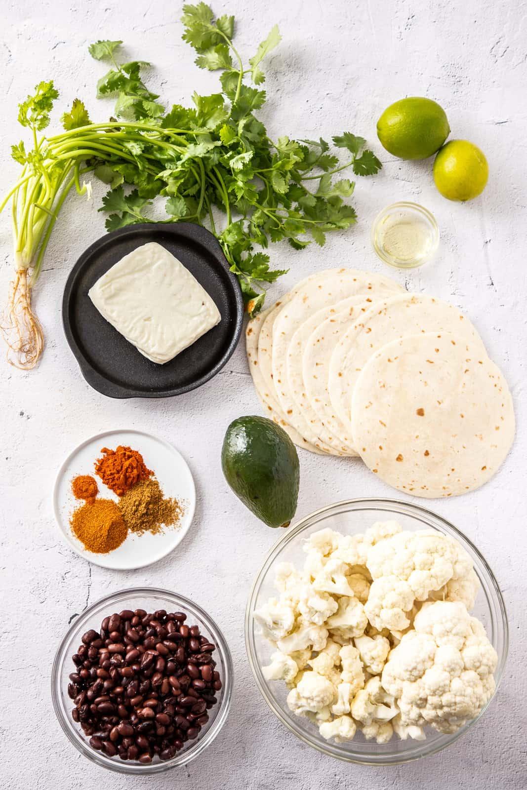 cauliflower, halloumi, black beans, spices, cilantro, lime, avocado, and soft taco shells on a white background