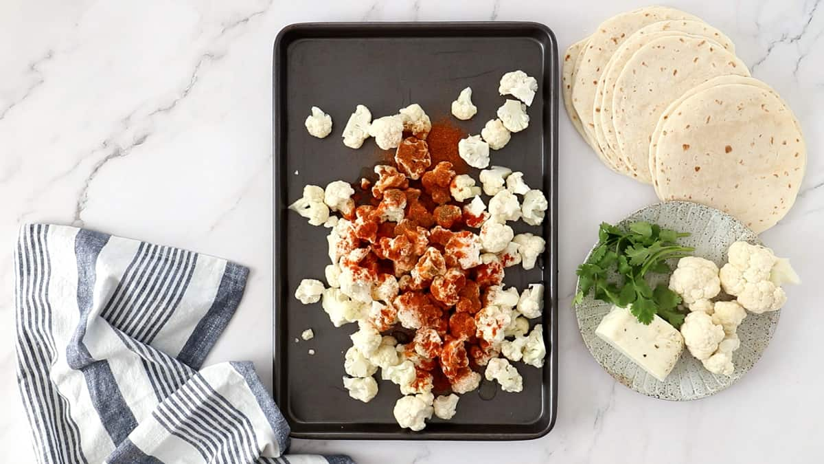 overhead photo of cauliflower and spices on a sheet pan