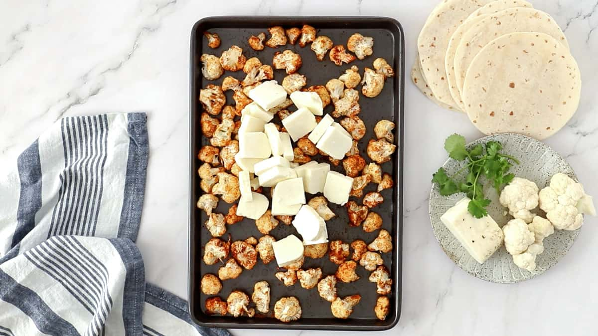 overhead photo of roasted cauliflower with halloumi added to a sheet pan