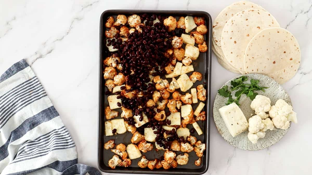 overhead photo of roasted cauliflower and halloumi with black beans added to a sheet pan