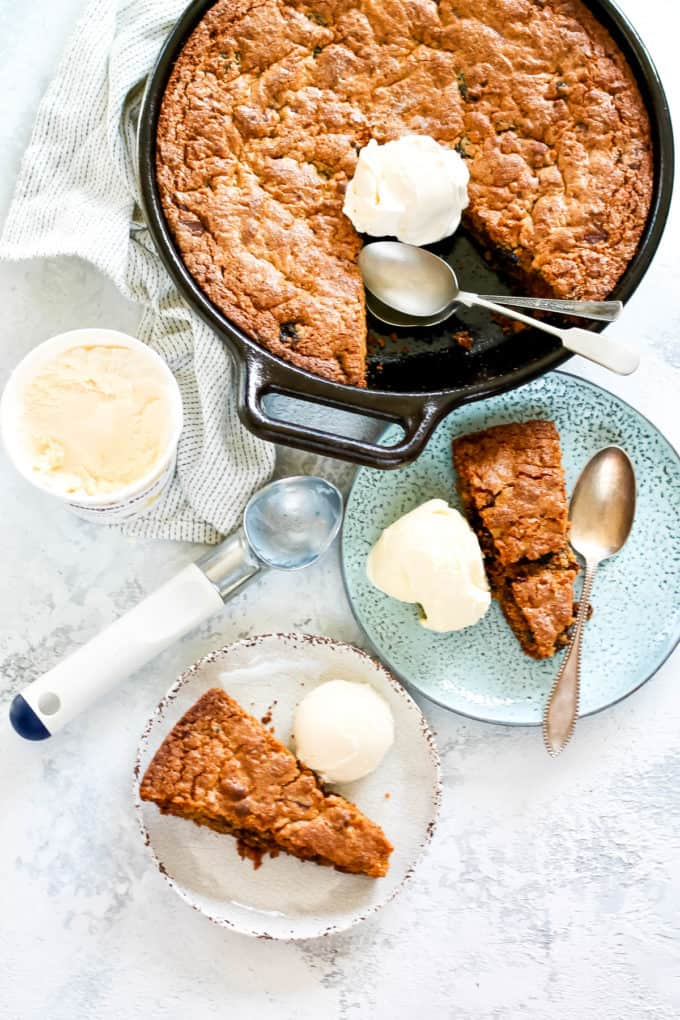 overhead photo with two slices of spelt flour cast iron skillet cookie on a white and blue plate