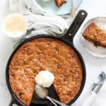 overhead photo of a cast iron skillet cookie topped with a scoop of vanilla ice cream