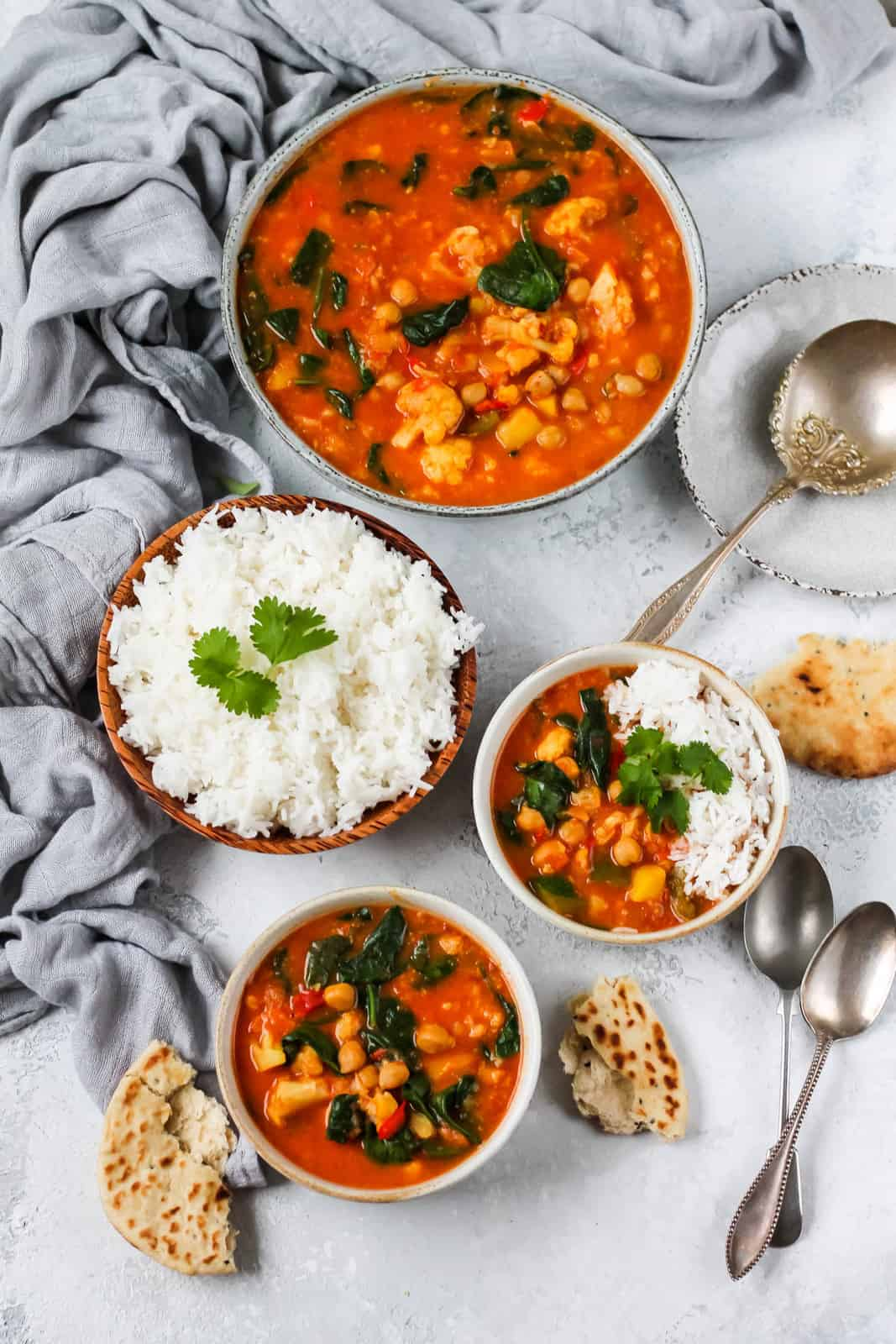 slow cooker chickpea curry in ceramic bowls on a grey background