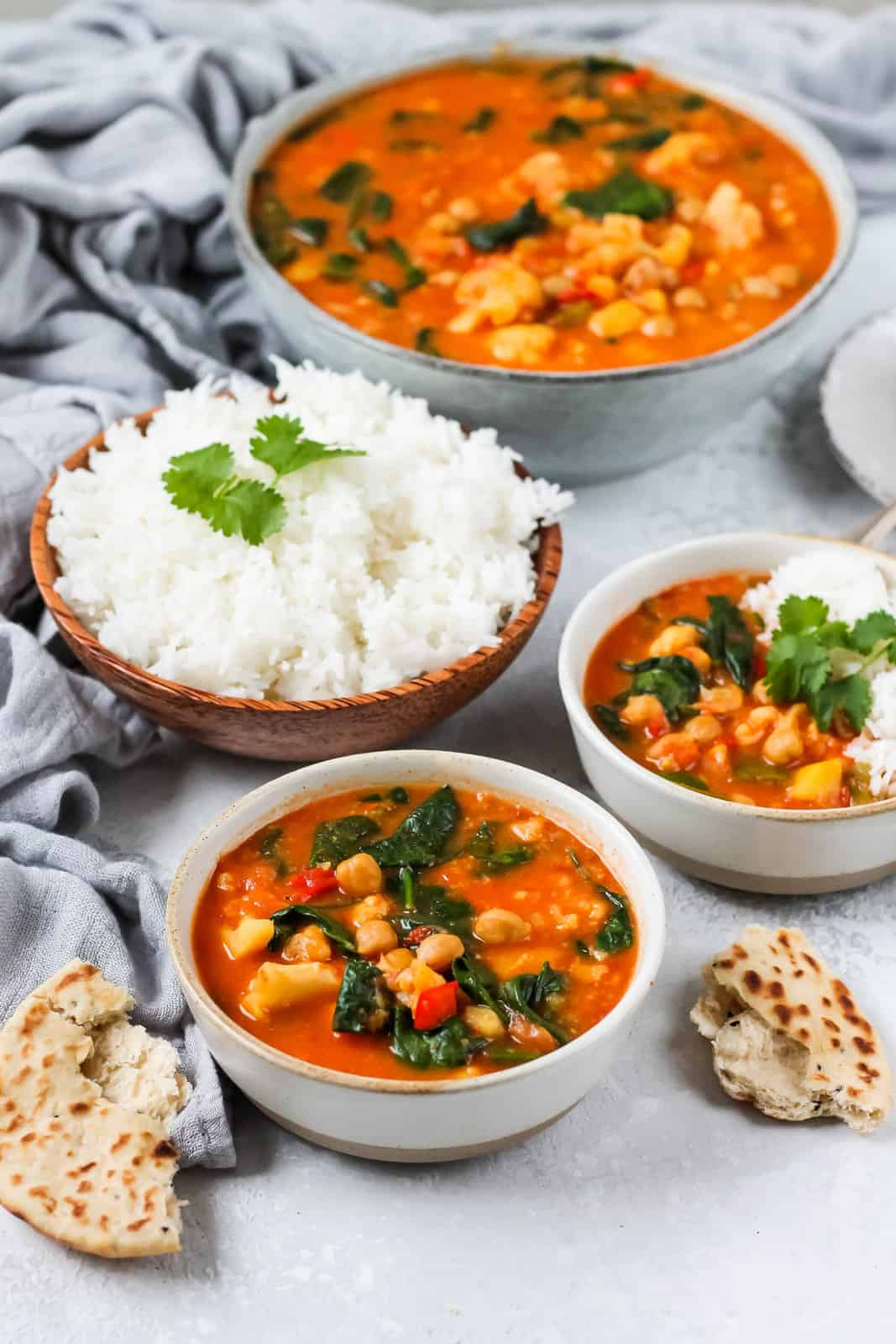 a bowl of chickpea curry on a grey background with rice and torn naan bread