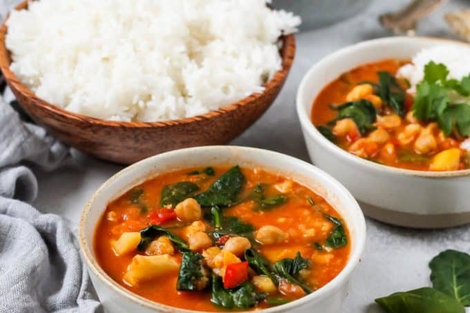 a bowl of vegan chickpea curry with a bowl of rice in the background
