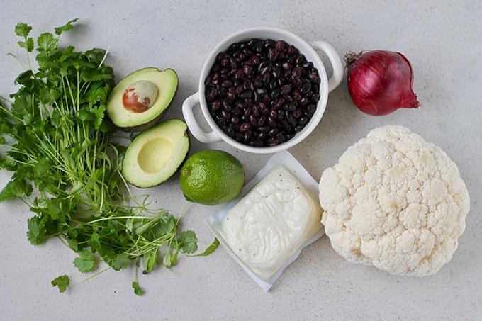 cilantro, avocado, limes, beans, halloumi, cauliflower and red onion on a grey background