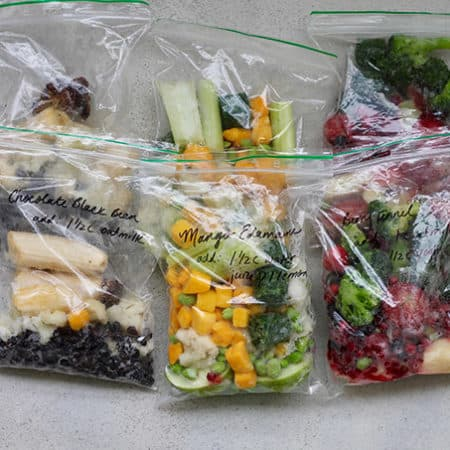 freezer bags packed with frozen fruits and vegetables on a grey background