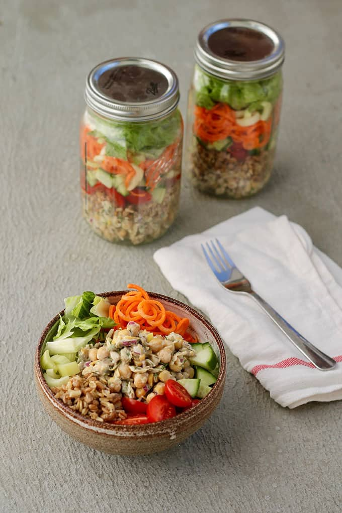 Mason jar salads and a bowl of salad on a grey background