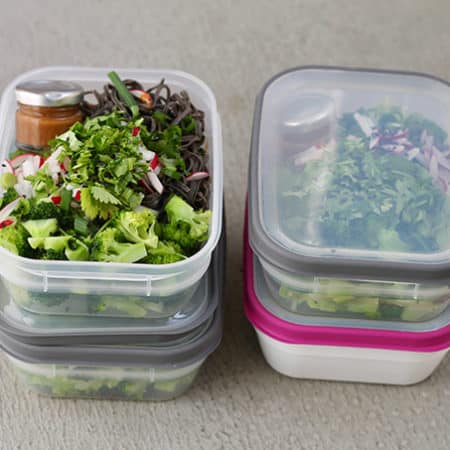 asian noodle salad packed into lunch boxes on a grey background