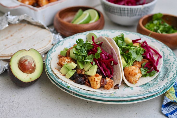 two cauliflower tacos on a pate topped with avocado, cilantro, and red cabbage