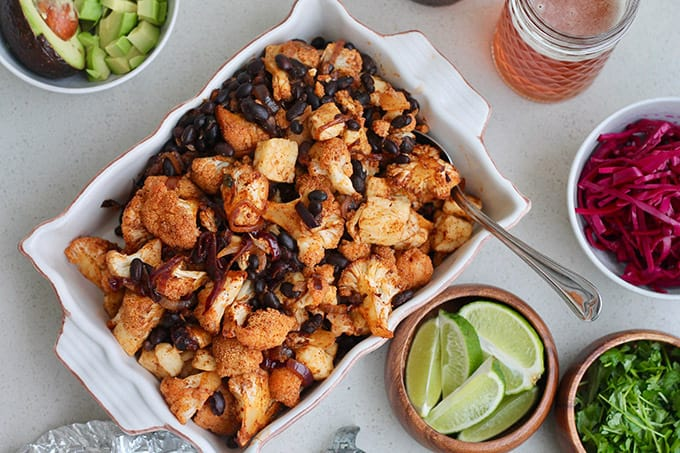 roasted cauliflower, halloumi, and black beans in a baking dish with taco toppings in the background
